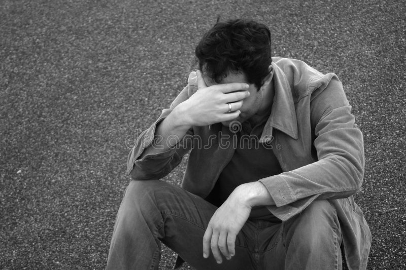 Sad Man. Man holds his head down in sadness royalty free stock images