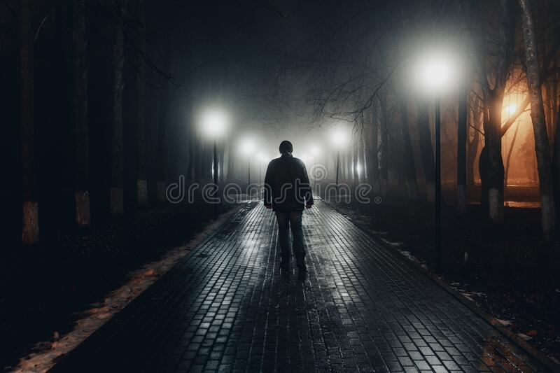 Sad man alone walking along the alley in night foggy park. Back view royalty free stock photography