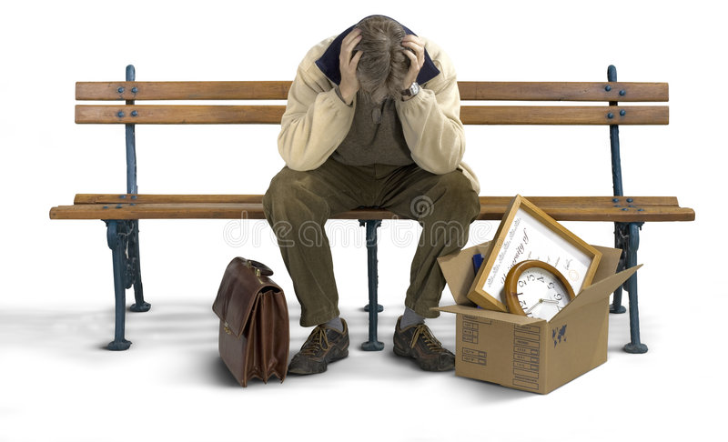 Sad man on a bench. Businessman siting on a bench looking depressed with his stuff packed in a box stock photo