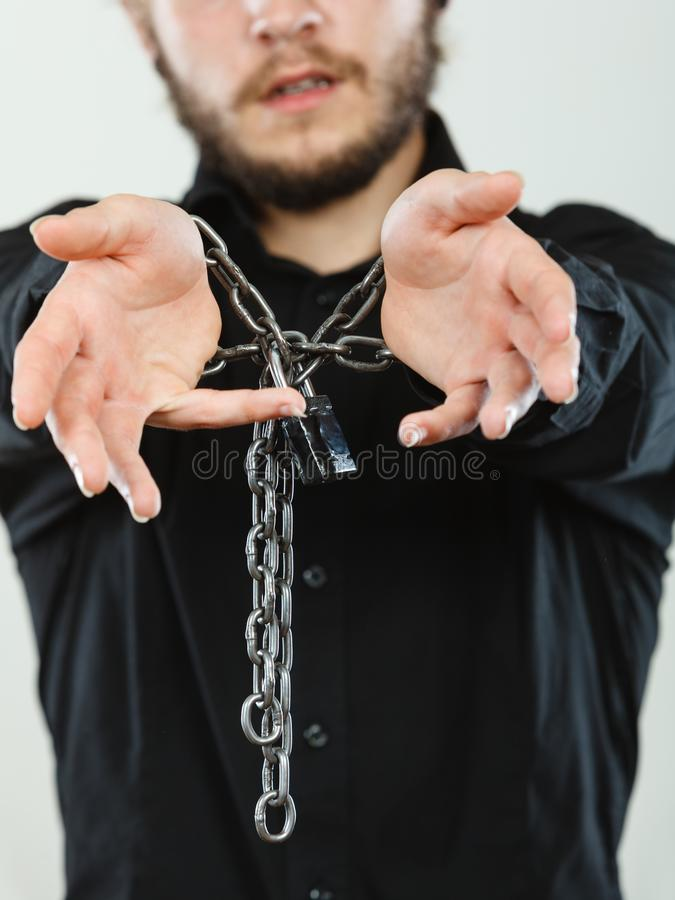 Sad man with chained hands, no freedom. No freedom, social problems concept. Sad man with chained hands, studio shot on light grey background stock images
