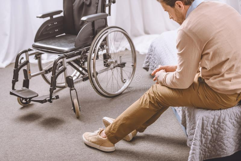 sad man with disability sitting on bed, wheelchair royalty free stock images