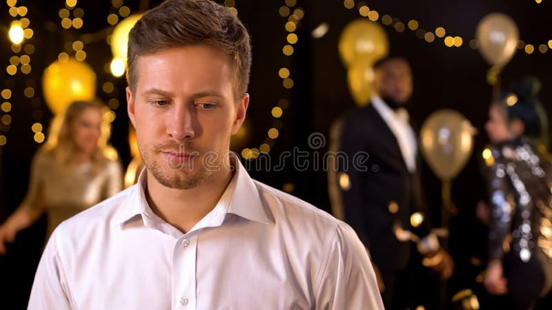 Sad man feeling lonely at party, dancing people on background, relations problem. Sad men feeling lonely at party, dancing people on background, relations royalty free stock images