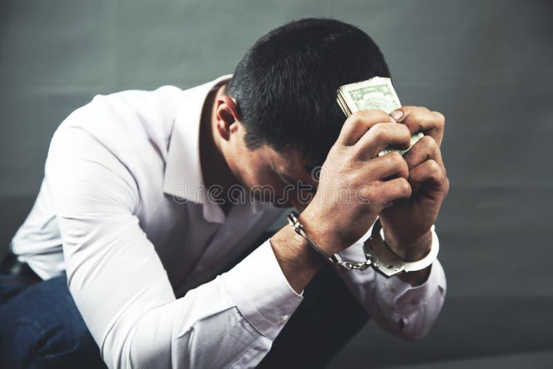 Sad man hand handcuffs with money royalty free stock image