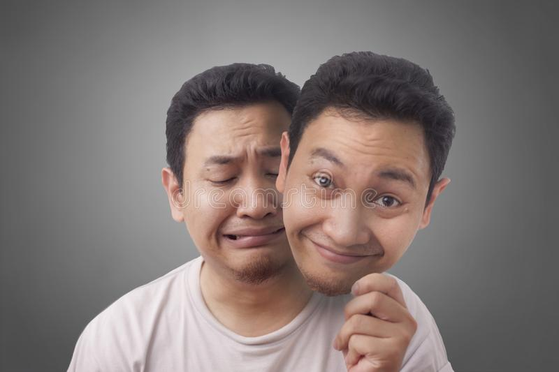 Sad Man with Happy Face Mask. Portrait of sad young Asian man disguise with happy face mask, sad man pretending to be happy indonesian malaysian thai self stock photography