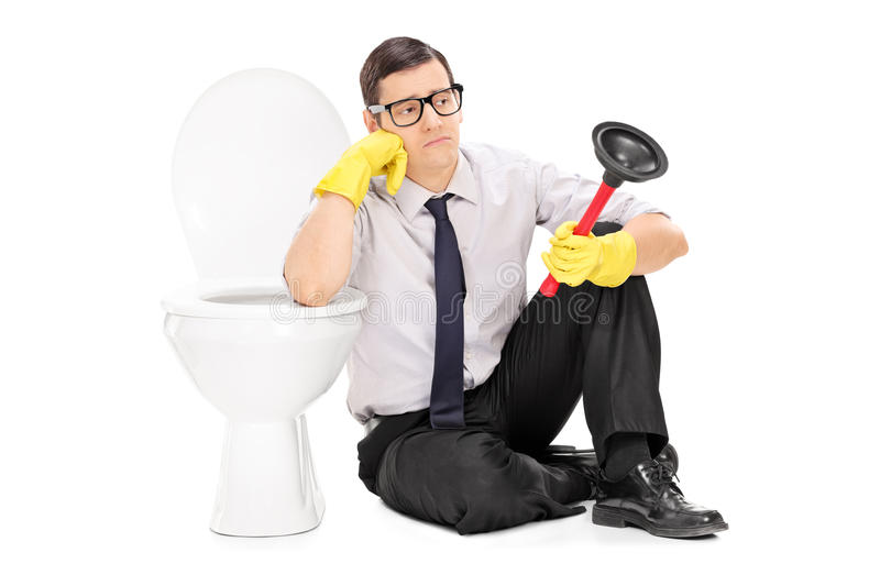 Sad man holding a plunger and sitting by a toilet. Isolated on white background stock photos