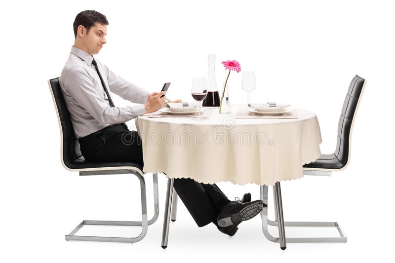 Sad man looking at his cell phone. Seated at a restaurant table isolated on white background stock image