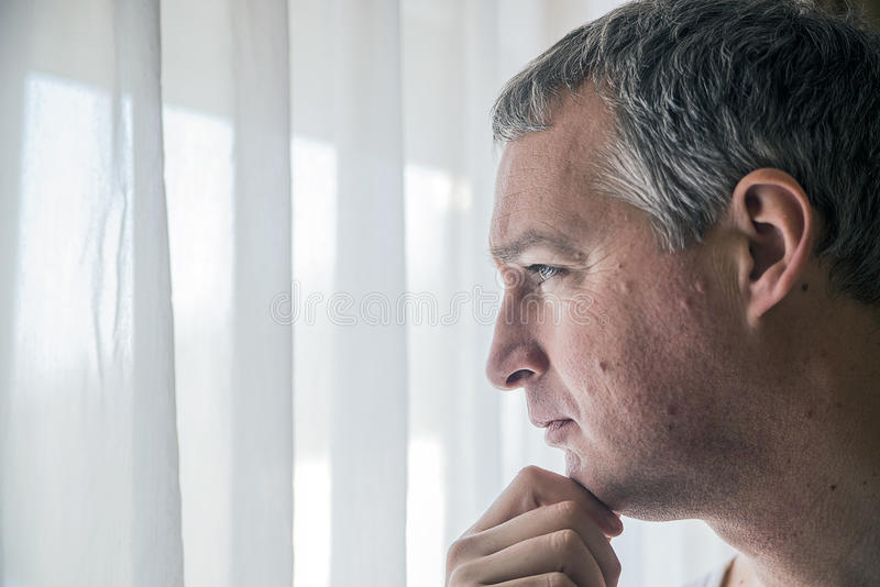 Sad man looking out the window. Feeling hopeless. Depressed mature man standing near the window royalty free stock photos