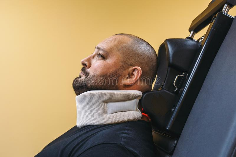 Sad man with neck brace on physical recovery treatment in clinic with special medical machine tool equipment. Or broken neck spine therapy concept royalty free stock photography