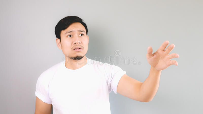 Sad man reaching hand as not to left him behind. An asian man with white t-shirt and grey background royalty free stock image