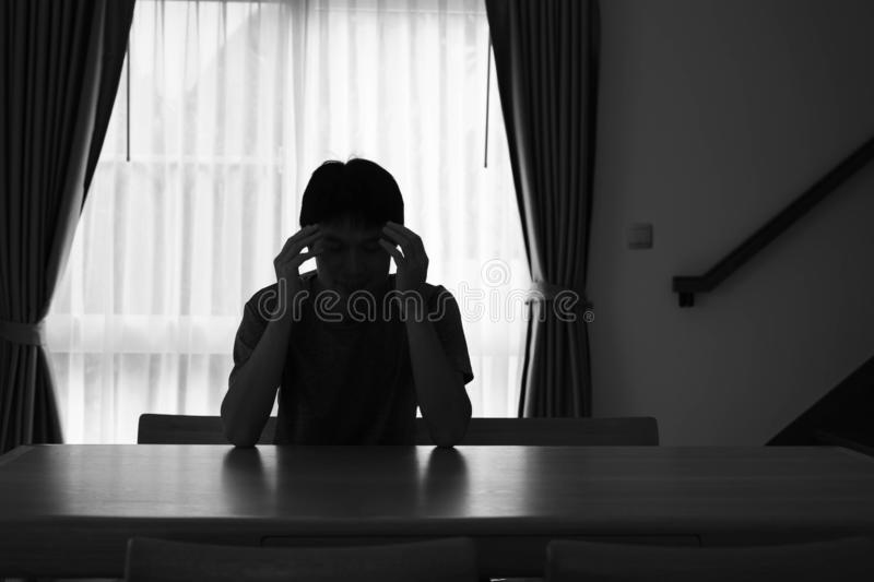 Sad man silhouette sitting on the table closed with curtains in home, Depression and anxiety disorder concept stock photography