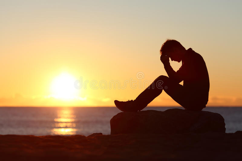 Sad man silhouette worried on the beach. At sunset with the sun in the background royalty free stock photo