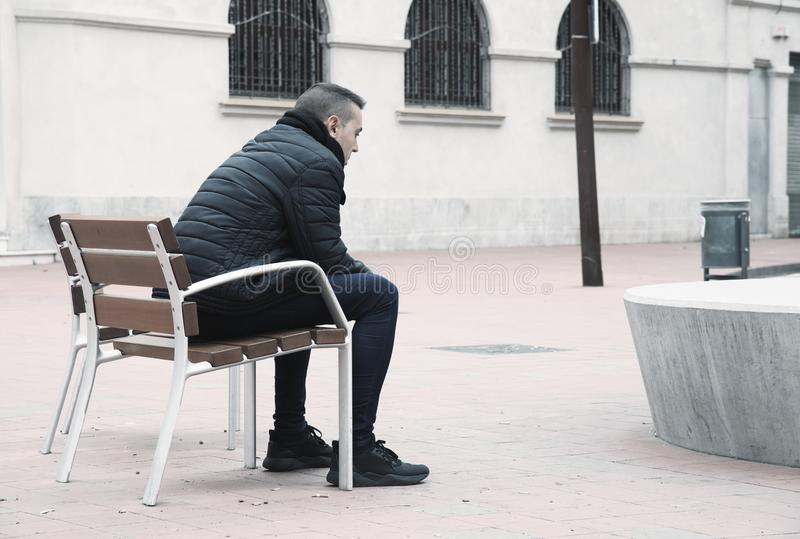 Sad man sitting in a bench in the street royalty free stock image