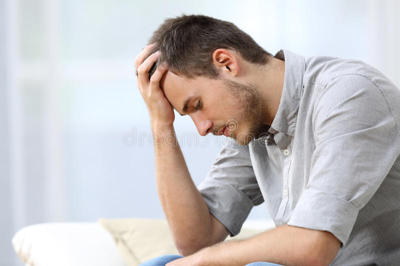 Sad man sitting on couch at home stock photography