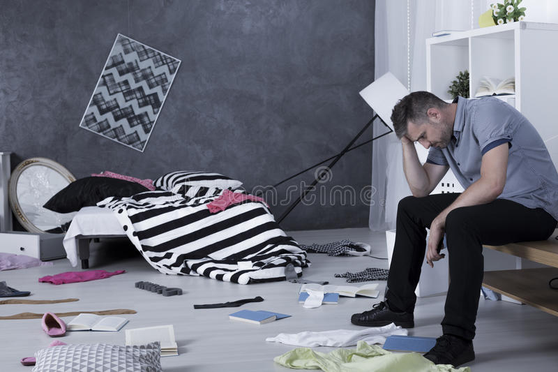 Sad man surrounded by mess. Sad man sitting on a table surrounded by mess stock photo