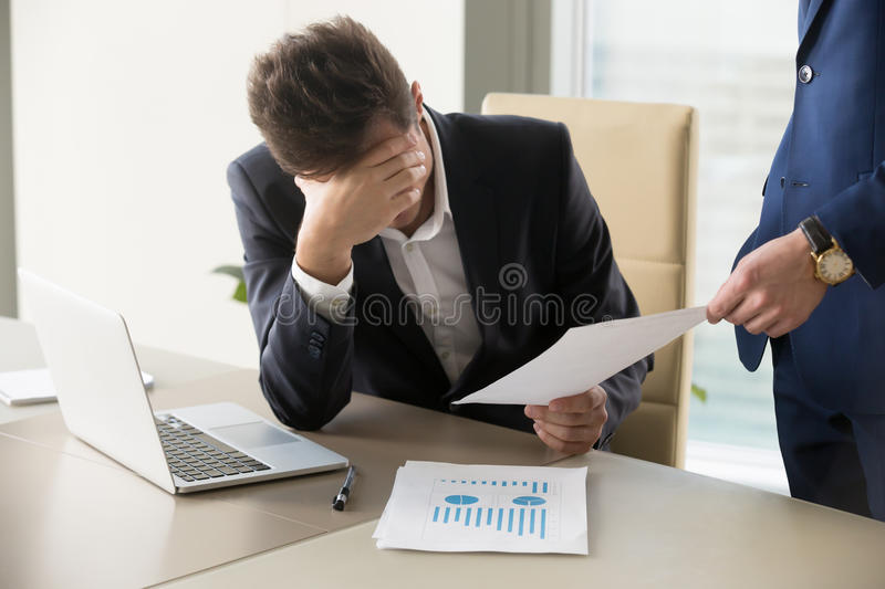 Sad manager getting notice of dismissal, document with bad news. Sad manager getting notice of dismissal, sitting at workplace with laptop and financial royalty free stock images