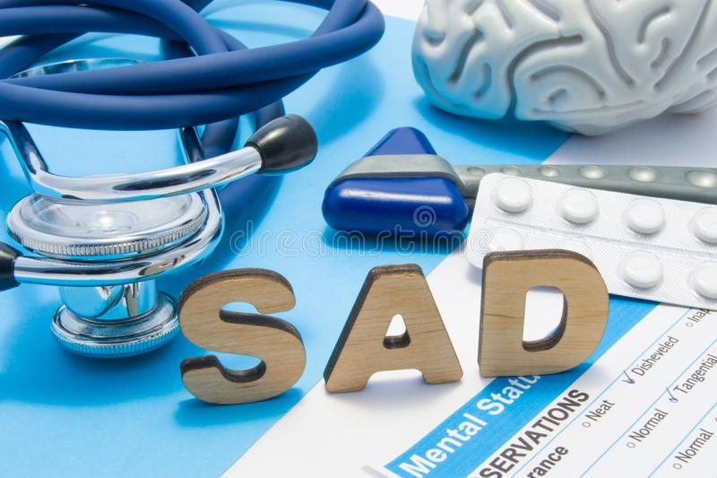 SAD medical abbreviation meaning seasonal affective disorder, depression could during seasons with little light. Word SAD is surro royalty free stock photo