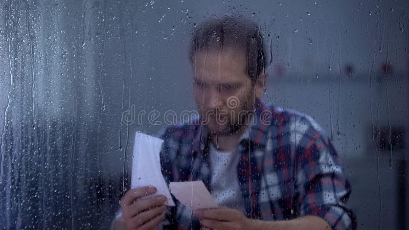 Sad middle-aged man putting together two parts of torn photo, missing wife. Stock photo royalty free stock photography