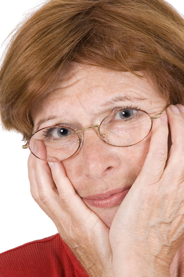 Sad middle aged woman. Portrait of sad middle aged woman with hands cupping face and glasses, white studio background stock photos