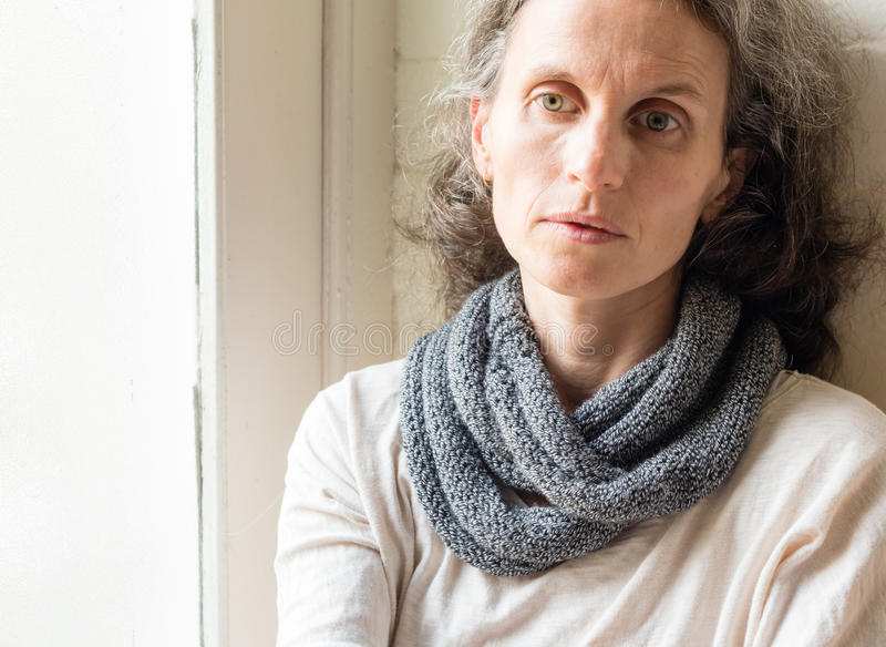Sad middle aged woman. Middle aged woman in grey scarf next to window looking sad and thoughtful royalty free stock images