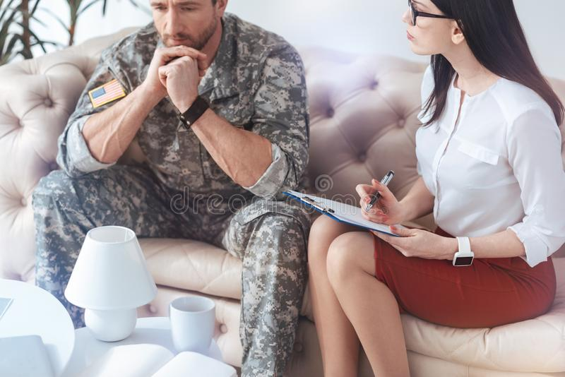 Sad military man talking about his worries at psychologist office. Psychological consequences of war. Troubled men sitting next to a young female therapist and royalty free stock photography