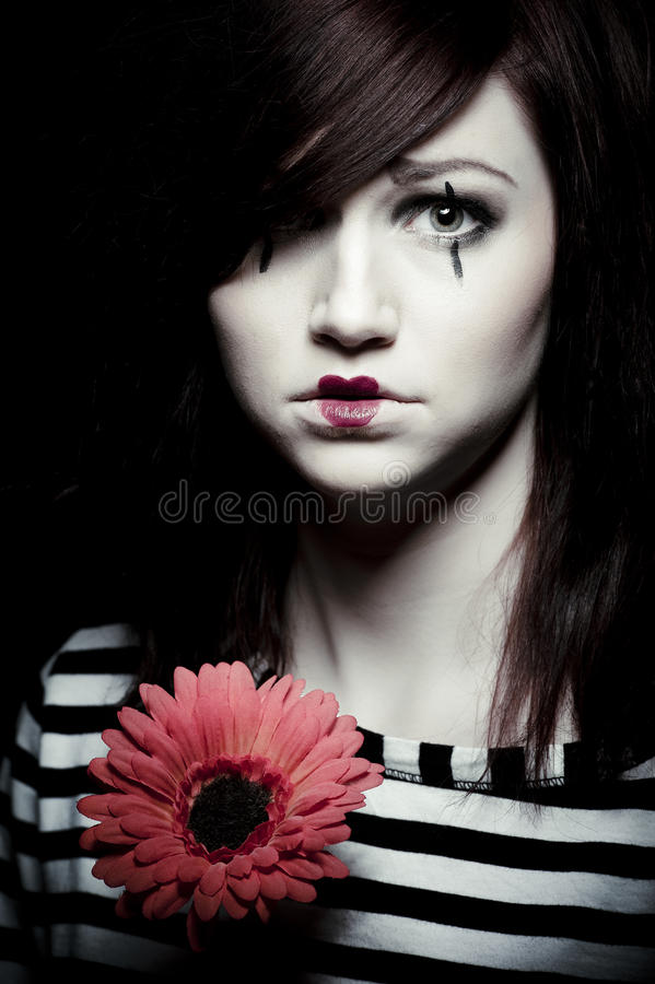 Sad mime. A sad female mime clown with a red flower royalty free stock photography