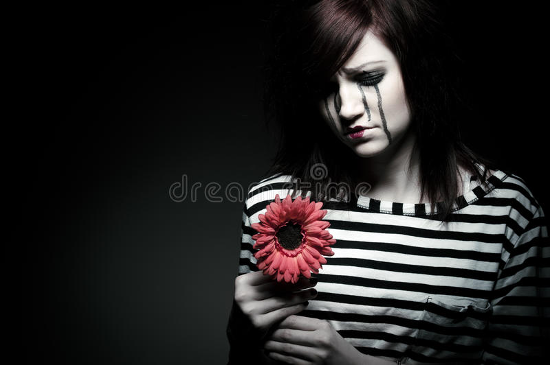 Sad mime. A sad female mime clown with a red flower stock image