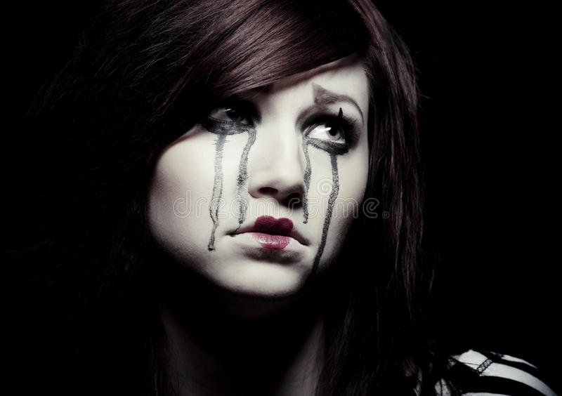 Sad mime. A sad female mime clown with a red flower stock images