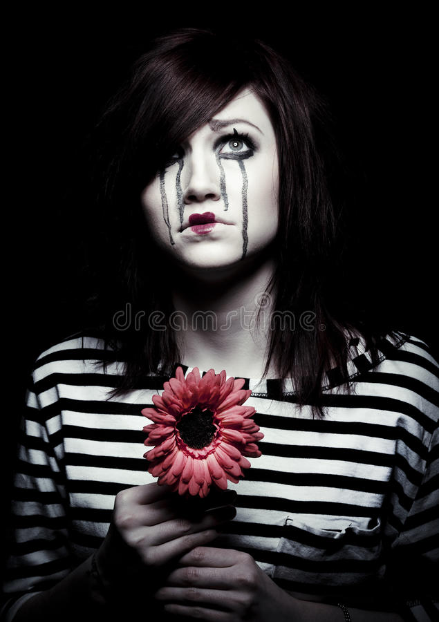 Sad mime. A sad female mime clown with a red flower royalty free stock photos