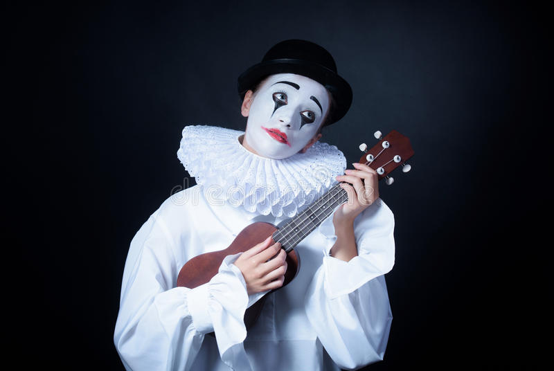 Sad mime Pierrot. Plays the small guitar royalty free stock images