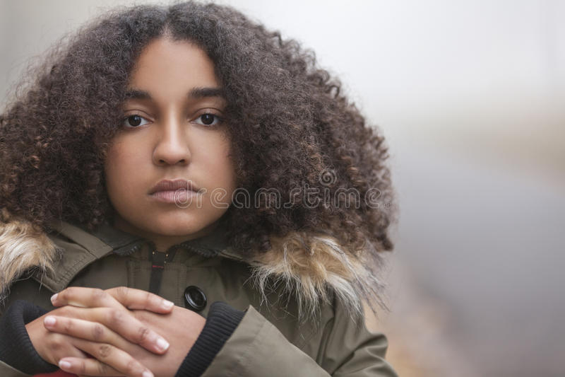 Sad Mixed Race African American Teenager Woman. Beautiful mixed race African American girl teenager female young woman outside in autumn or fall mist or fog royalty free stock photos