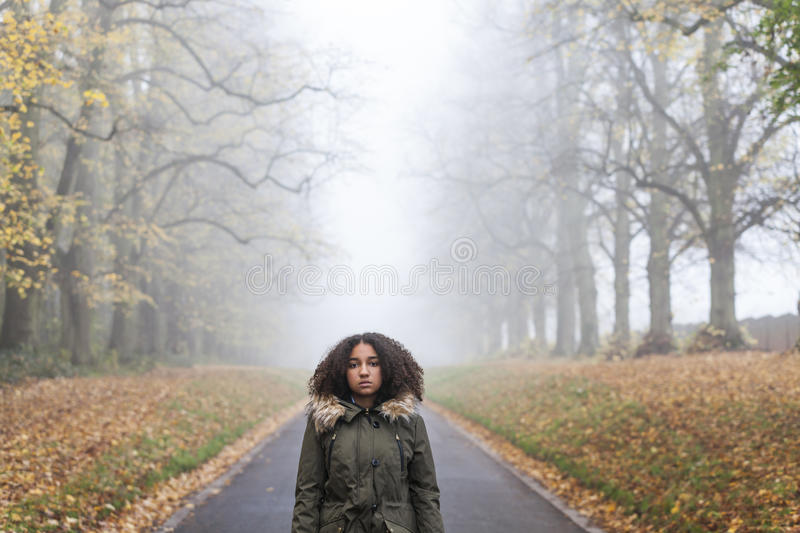 Sad Mixed Race African American Teenager Woman. Beautiful mixed race African American girl teenager female young woman standing outside on a road in autumn or stock photo