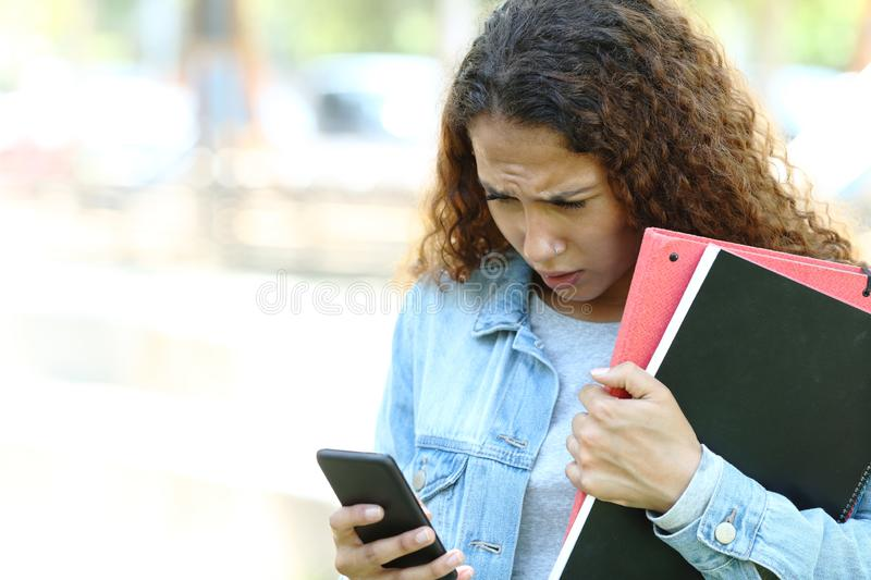 Sad mixed race student checking phone messages. Sad mixed race student checking smart phone messages standing in a park or campus stock photo
