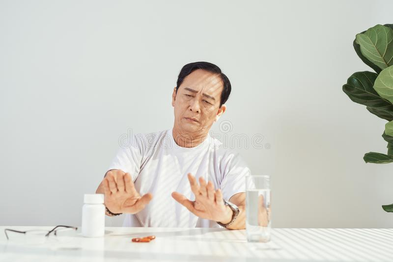 Sad mood. Low angle shot of an upset elderly man sitting while taking his medication royalty free stock images