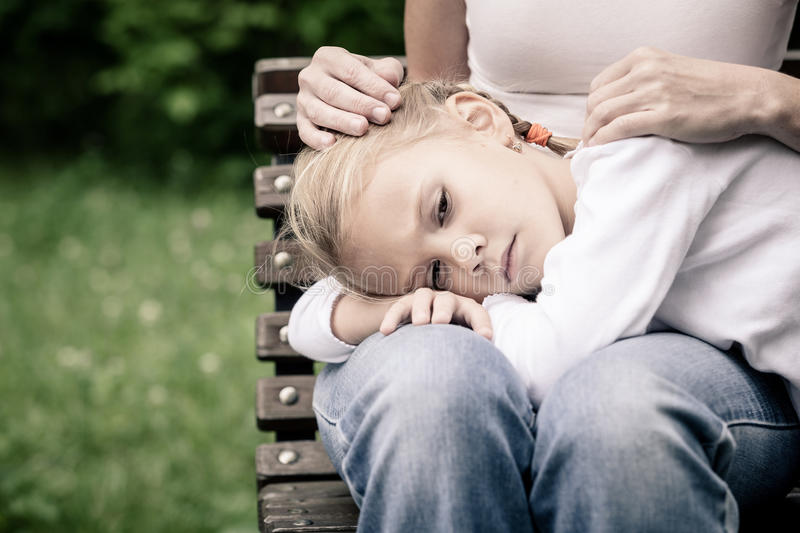 Sad mother and daughter sitting on bench in the park royalty free stock images