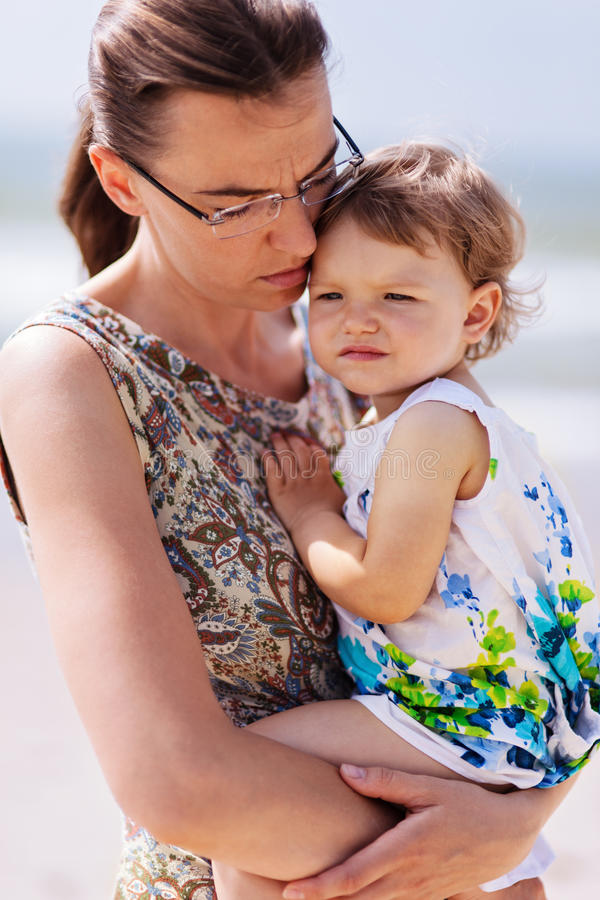 Sad mother holding daughter royalty free stock photo