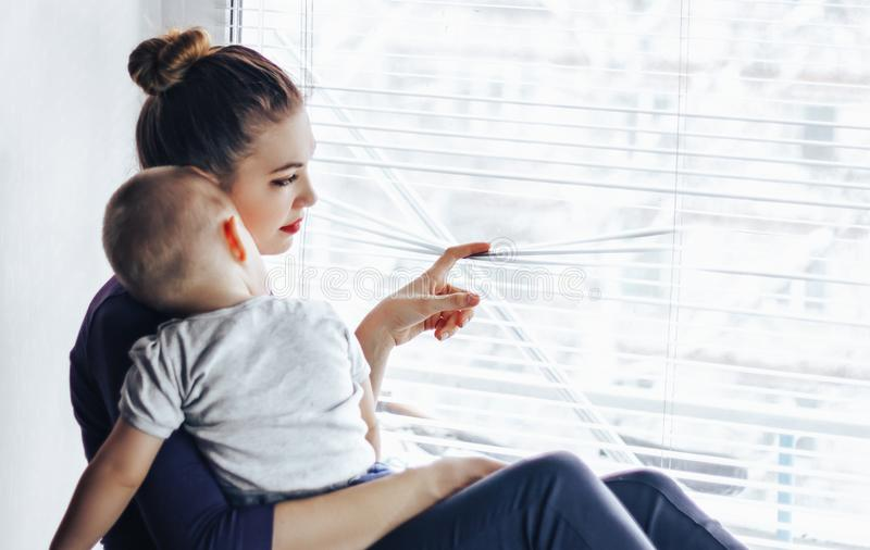A sad mother sitting with her baby on the windowsill, looking out the window and waiting for something. The baby is lying on Mom` stock images