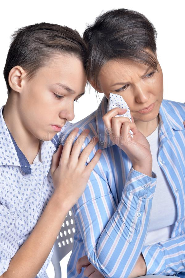 Sad mother and son posing on white background stock image