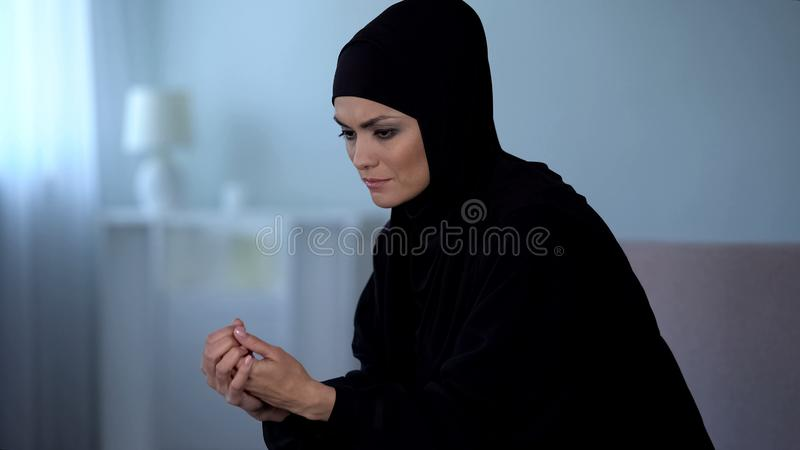 Sad muslim woman in black hijab sitting on sofa, thinking about problem, crisis royalty free stock photography