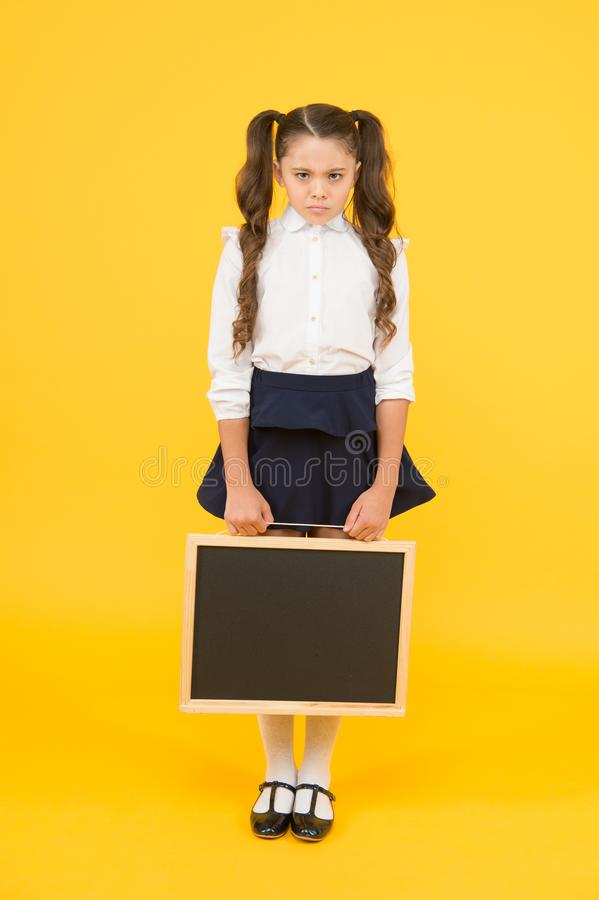 Sad news. Schoolgirl offended pupil informing you. School girl hold blank chalkboard copy space. Announcement and royalty free stock images