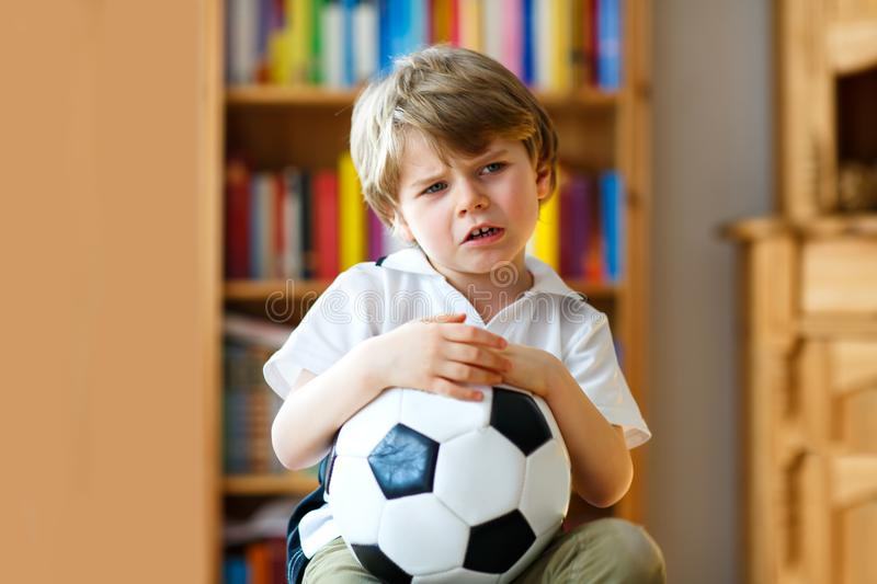 Sad and not happy little kid with football about lost football or soccer game. child after watching match on tv royalty free stock photo