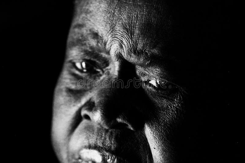 A sad old African woman looks on in despair stock photos