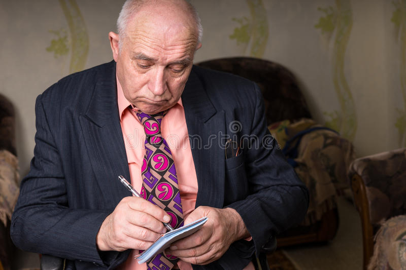 Sad Old Businessman Writing on his Small Notes stock images