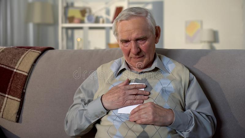 Sad old male with tears on face hugging wife photo missing family, loneliness. Stock photo stock photography