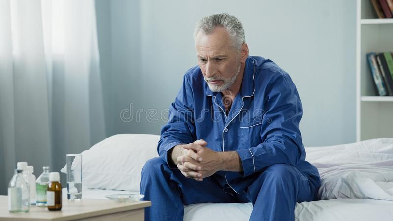 Sad old man sitting in bed and looking at pills, medication and healthcare stock photos