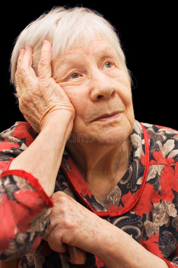 The sad old woman on the black. Background royalty free stock photos