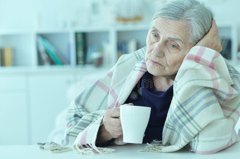 Sad old woman with headache drinking tea. Portrait of a sad old woman with headache drinking tea stock photography