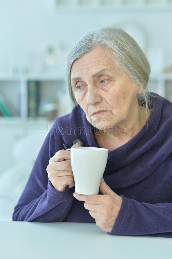 Sad old woman with headache drinking tea. Portrait of a sad old woman with headache drinking tea stock images
