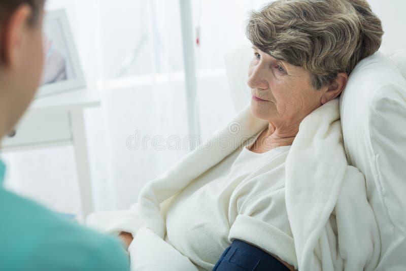 Sad old woman at hospital. Photo of nurse and sad old women at hospital stock photos