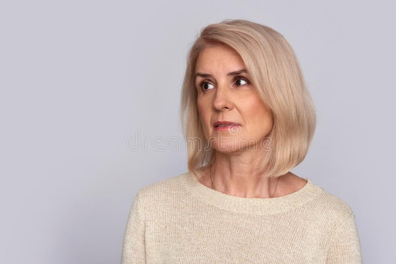 Sad old woman looking away. Isolated. Sad old woman looking away to copy space. Isolated on grey. Studio shot royalty free stock image