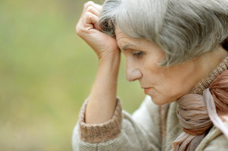 Sad old woman. Nice sad old woman on the autumn background royalty free stock photography